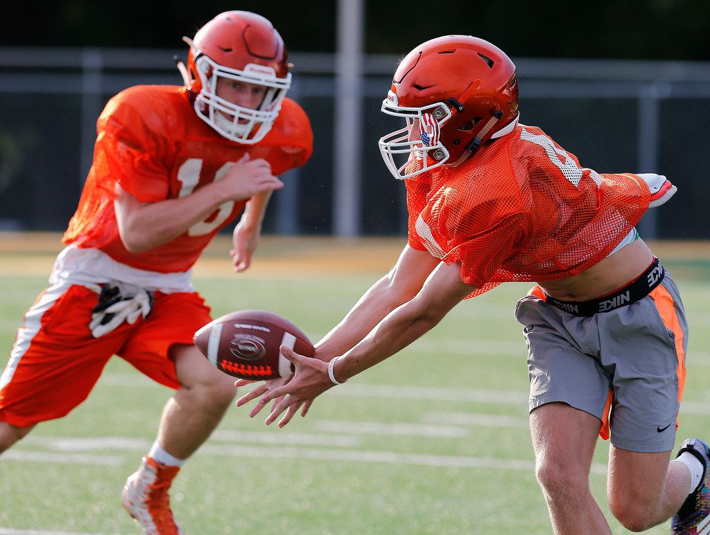 Jake Urbanowski (right) receives a pass while Parker Holman defends while taking part in a drill during the first week of football practice for Celina High School at Bobcat Stadium on Wednesday, August 8, 2018.