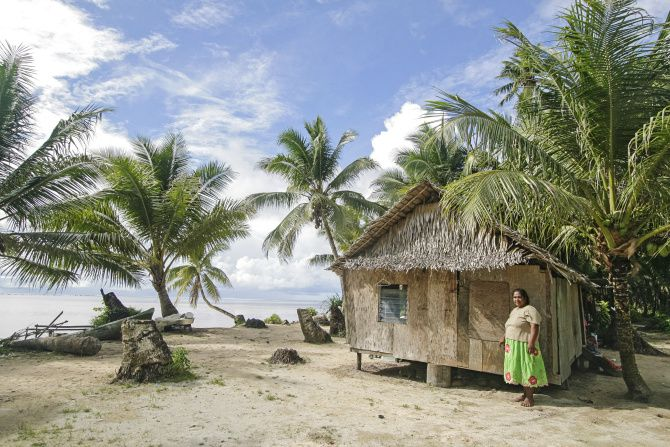 Local woman stands by her palm thatch house in Walung, an isolated village in Kosrae, Federated States of Micronesia (FSM).