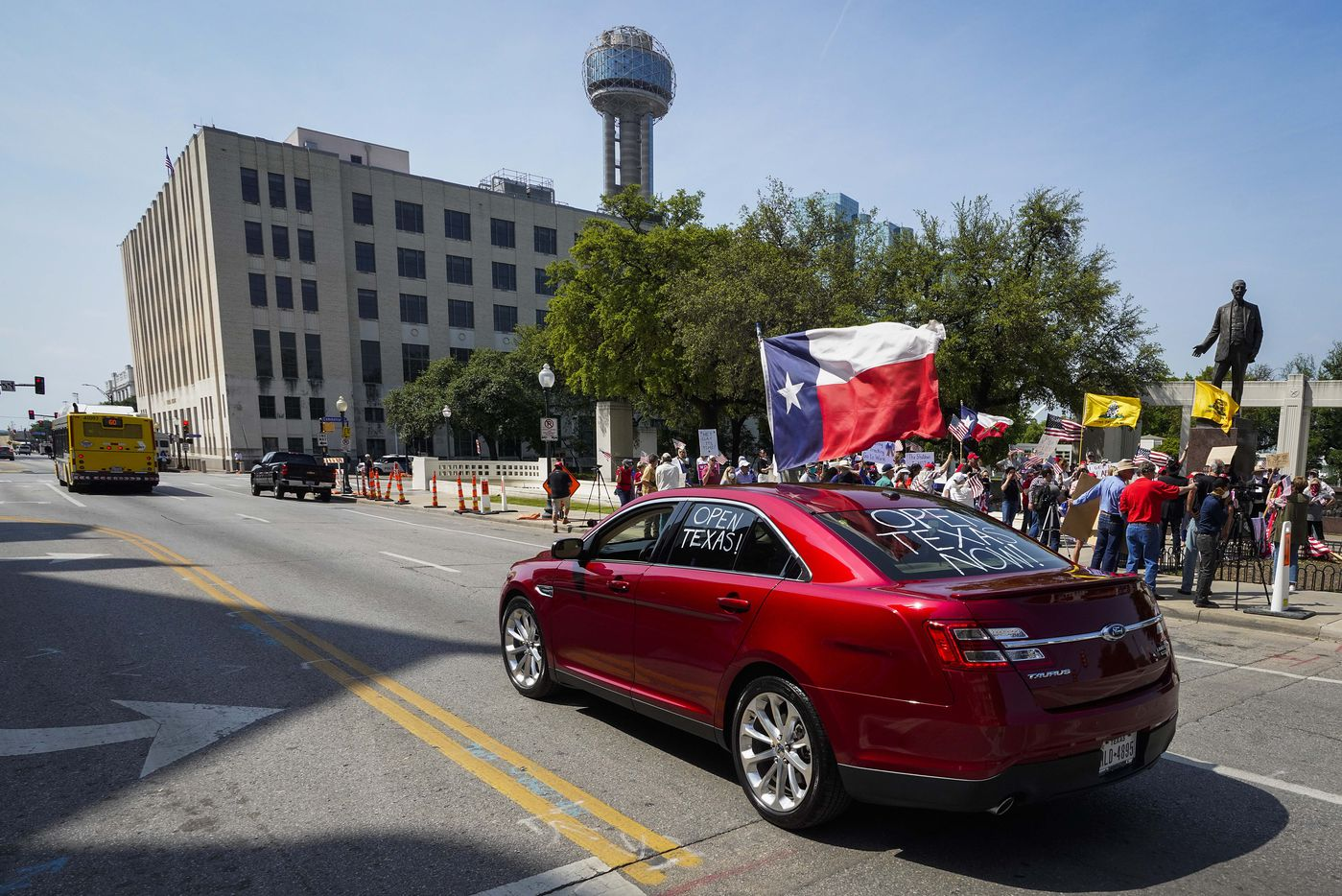 A driver in a car marked with the words ÔOpen TexasÓ passes as protestors rally against government stay-at-home orders at Dealey Plaza on Tuesday, April 21, 2020, in Dallas.