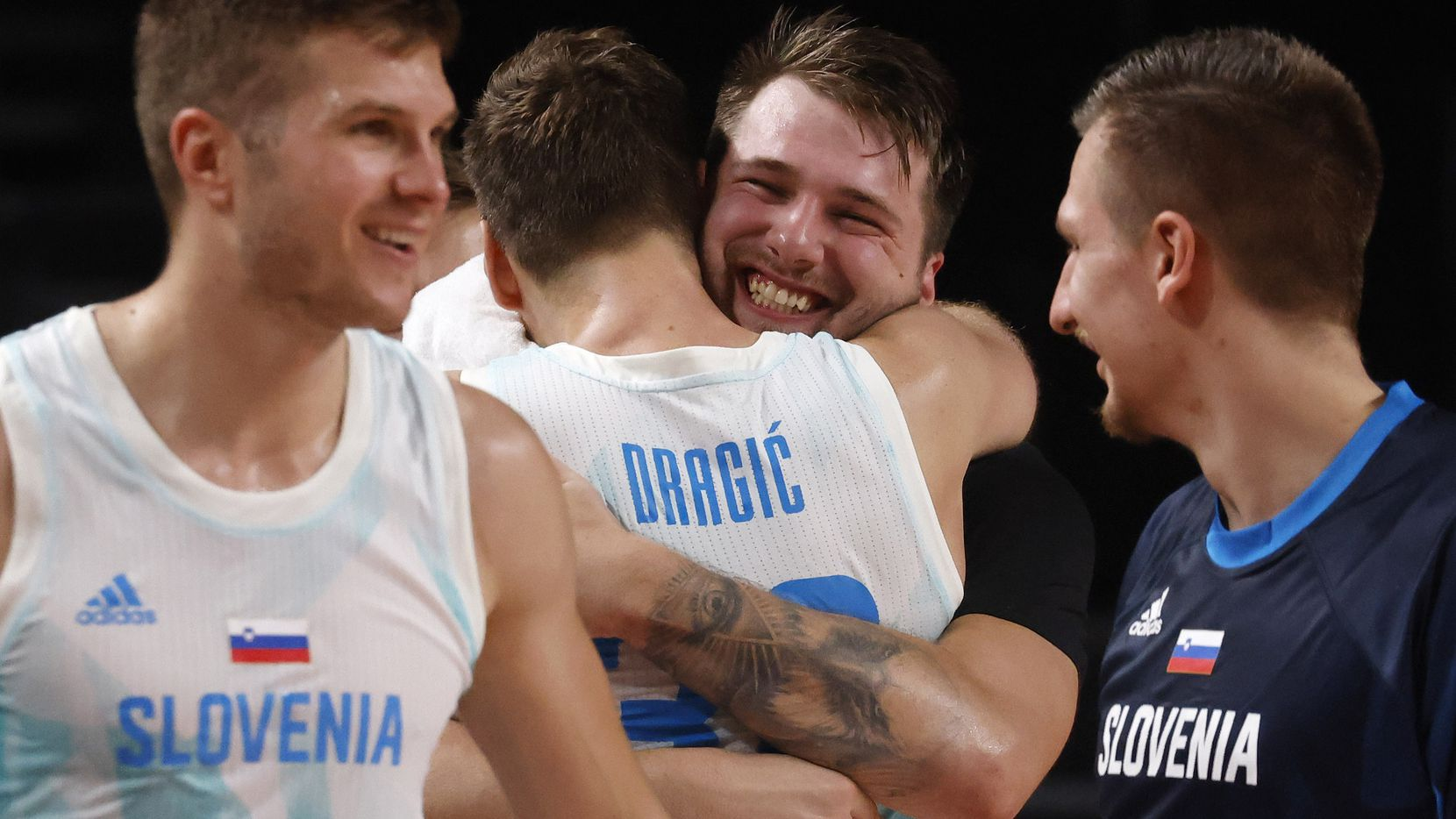 Slovenia's Luka Doncic (77) hugs Zoran Dragic (30) after both were pulled from play late in the game against Germany during the second half of play of a quarter final basketball game at the postponed 2020 Tokyo Olympics at Saitama Super Arena, on Tuesday, August 3, 2021, in Saitama, Japan. Slovenia defeated Germany's 94-70.