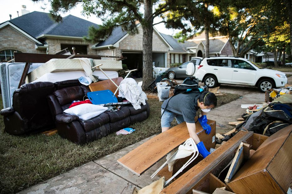 Chumming Xu looks through his flood damaged belongings in the aftermath of Hurricane Harvey on Thursday, Sept. 7, 2017, at the Canyon Gate community in Katy, Texas. (AP Photo/Matt Rourke)