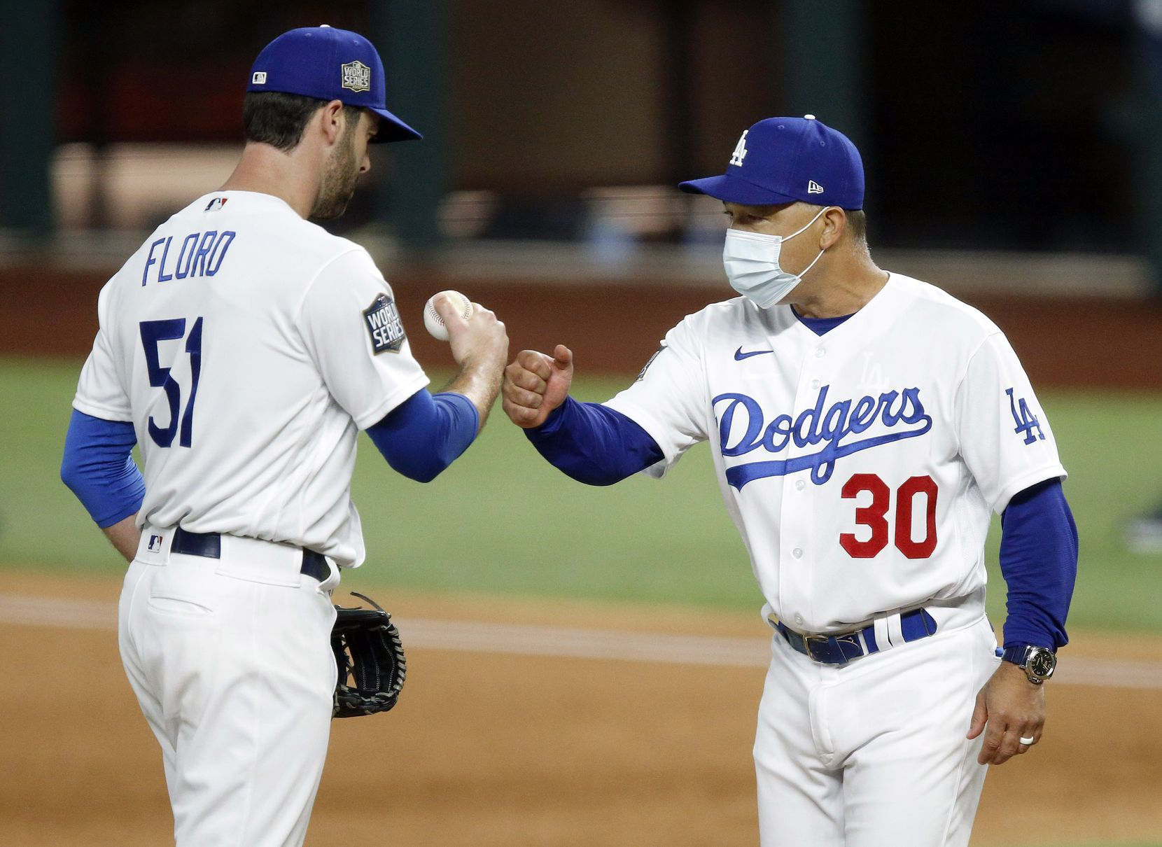 Los Angeles Dodgers manager Dave Roberts gives relief pitcher Dylan Floro (51) a fist bump as he pulls him from the game during the third inning against the Tampa Bay Rays in Game 2 of the World Series at Globe Life Field in Arlington, Wednesday, October 21, 2020. (Tom Fox/The Dallas Morning News)