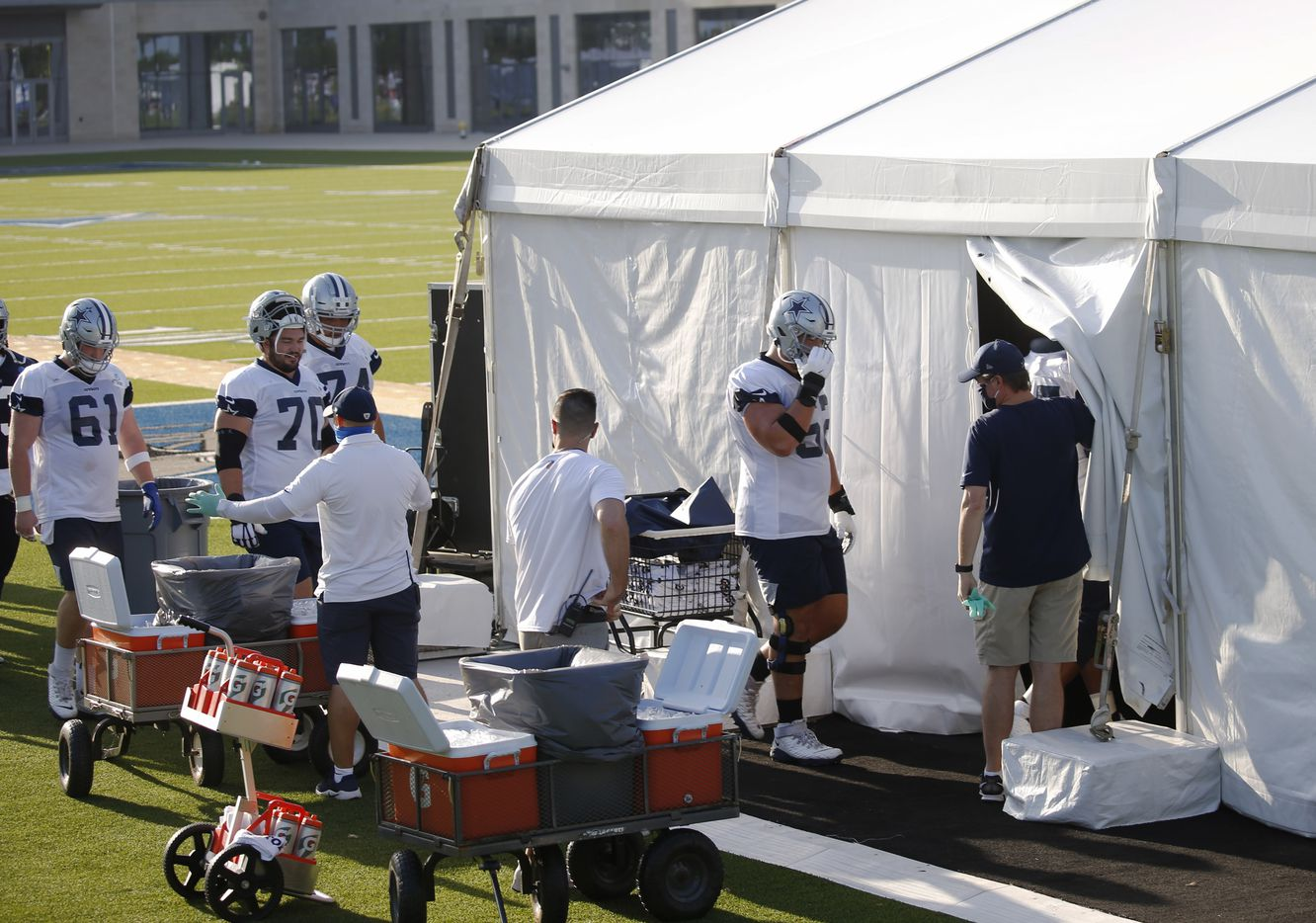 Dallas Cowboys center Marcus Henry (62) and other Dallas Cowboys players make their way into an air conditioned tent on the field during the first day of training camp at Dallas Cowboys headquarters at The Star in Frisco, Texas on Friday, August 14, 2020. (Vernon Bryant/The Dallas Morning News)