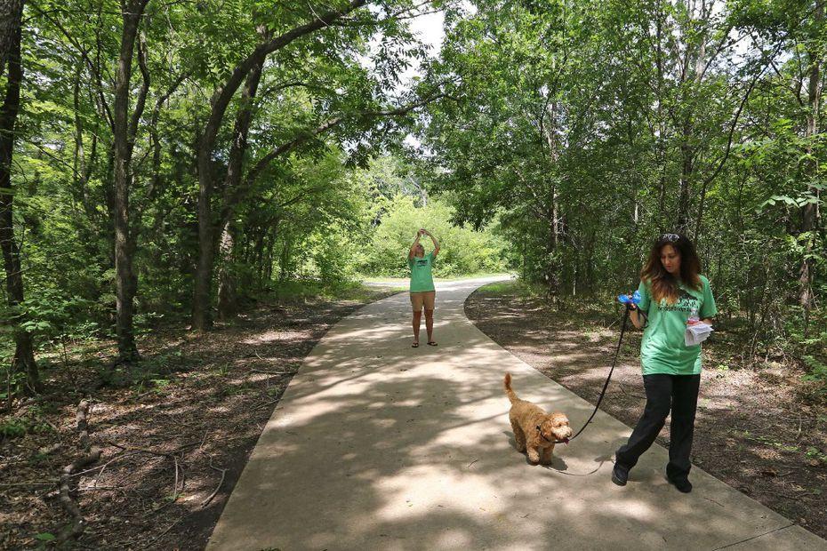 Dana McCormick (background) takes a photo as Diana Nowlin walks McCormick's dog Romero along a trail near where a proposed traffic bridge would be built.