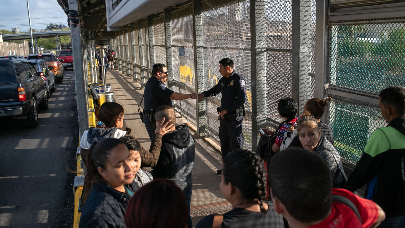 Agentes de migración vigilan la entrada al puente internacional que conecta a Matamoros, México, con Brownsville, Texas.