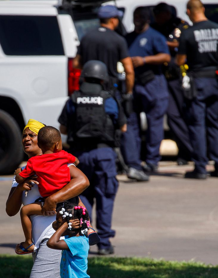 A young girl passing along the sidewalk covers her ears after a flash bang was then set off by Dallas Police Department SWAT officers working the scene where someone shot at officers attempting to make an arrest at an east Oak Cliff apartment complex on Thursday, July 13, 2017, in Dallas.