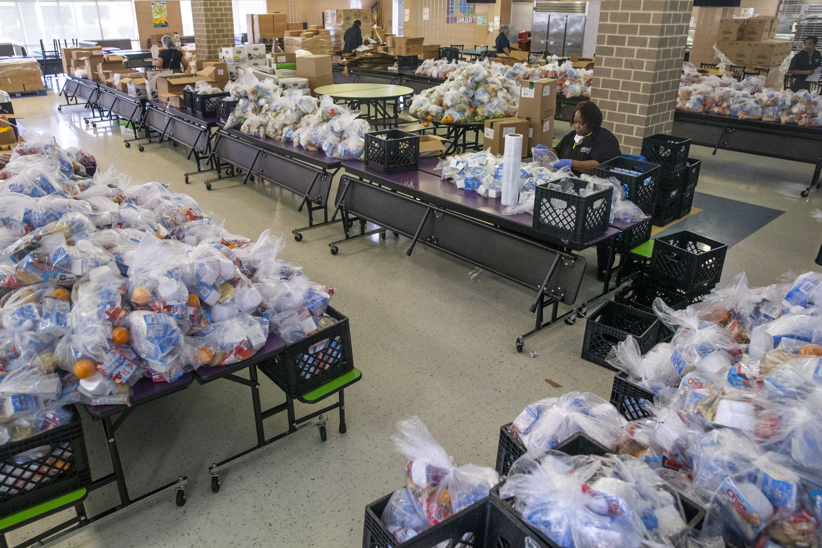 Dallas ISD employees and volunteers prepared bagged breakfasts, lunches and suppers for students at Medrano Middle School in Dallas on Thursday. For many students' families, normal food insecurity has been exacerbated by COVID-19 closures.