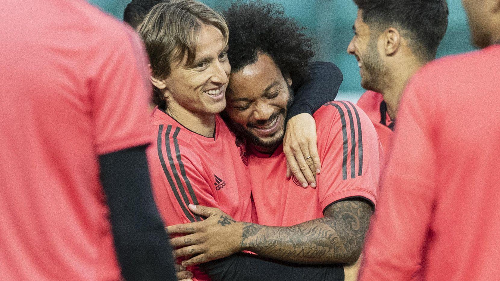 Luka Modric (izq.) abraza a Marcelo, su compañero en el Real Madrid, que el miércoles enfrenta su primer compromiso importante desde la salida de Cristiano Ronaldo y Zinedine Zidane. (AP/Pavel Golovkin)