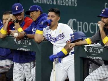 Texas Rangers catcher Yohel Pozo (center) and his batting coach Luis Ortiz (center, left) and manager Chris Woodward (right) watch their team at bat against the Colorado Rockies in the seventh inning at Globe Life Park in Arlington, Texas Wednesday, September 1, 2021.