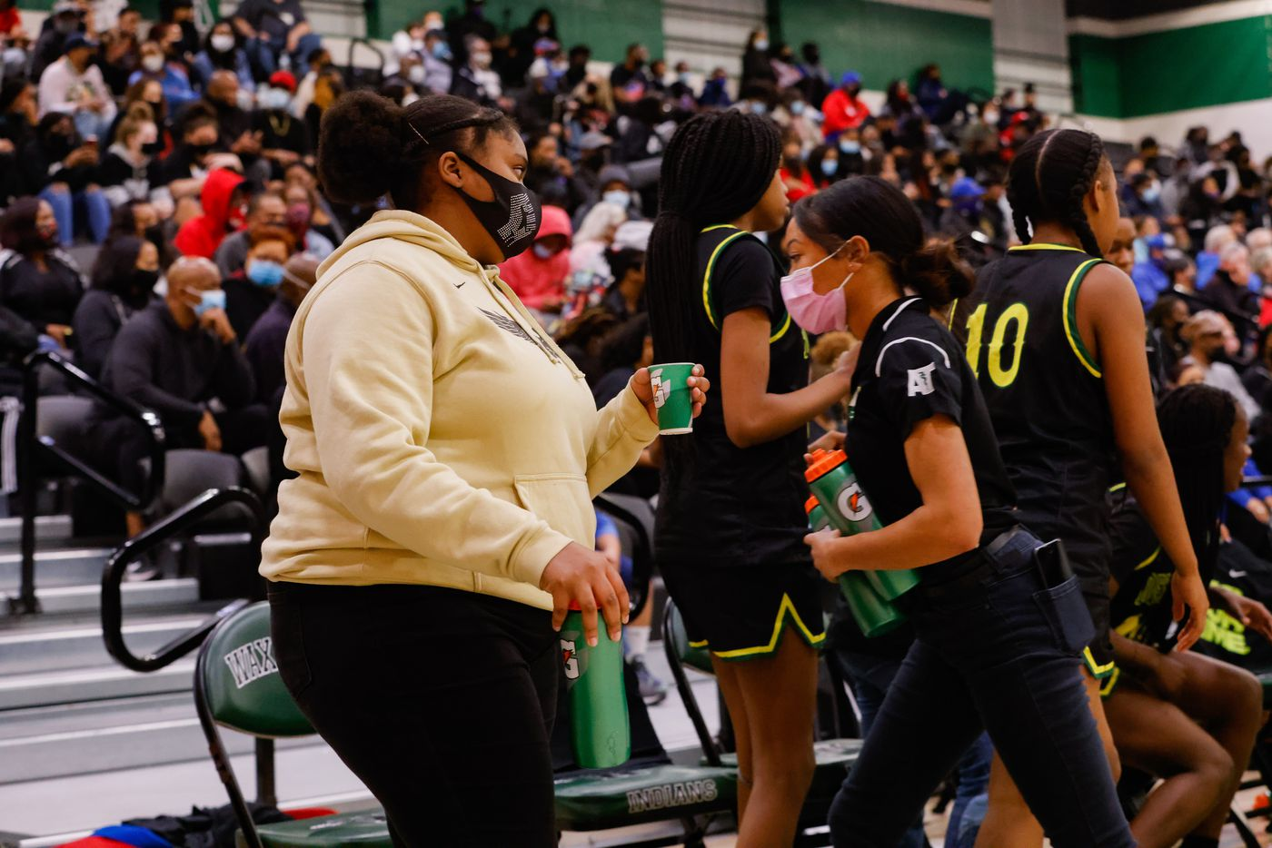 DeSoto's student trainers Corrie Crawford (left) and Khiya Cockerham prepare water for the players during the second half of a girls basketball Class 6A Region II UIL game against Duncanville in Waxahachie on Tuesday, March 2, 2021. DeSoto won the game 52-39. (Juan Figueroa/ The Dallas Morning News)