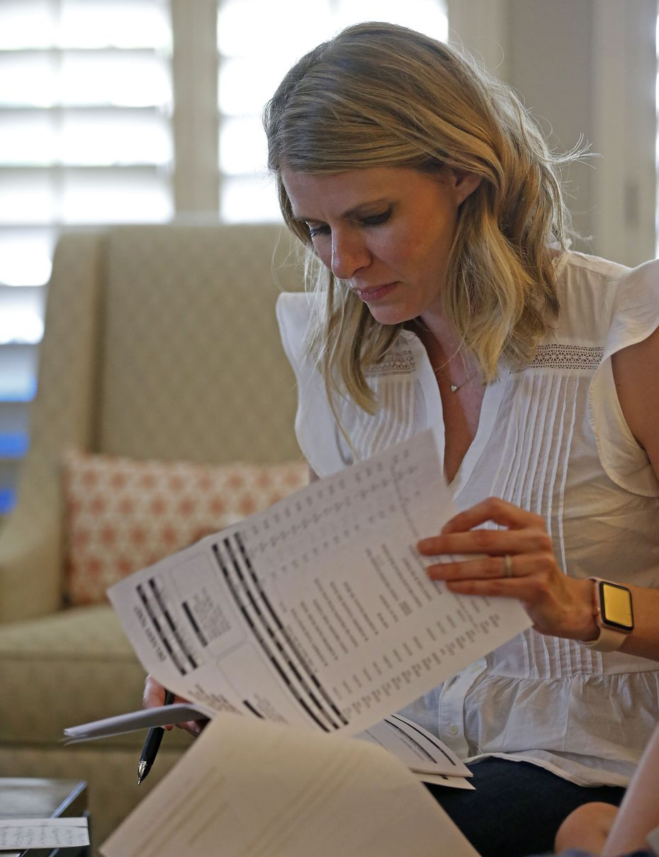 Kasey Woleben looks at a medical bill in the living room at her home in McKinney, Texas, Wednesday, June 20, 2018.