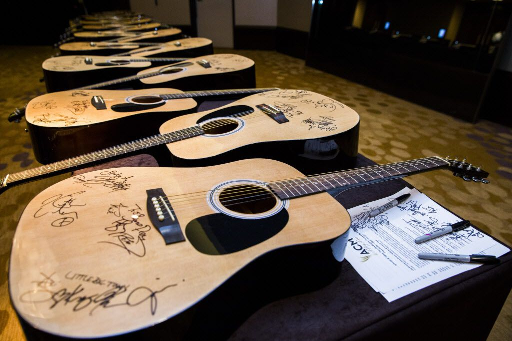 Guitars signed by country music artists are displayed on tables near the red carpet at the ACM Lifting Lives gala. The guitars were to be given to donors or auctioned to raise money for charities supported by ACM Lifting Lives.