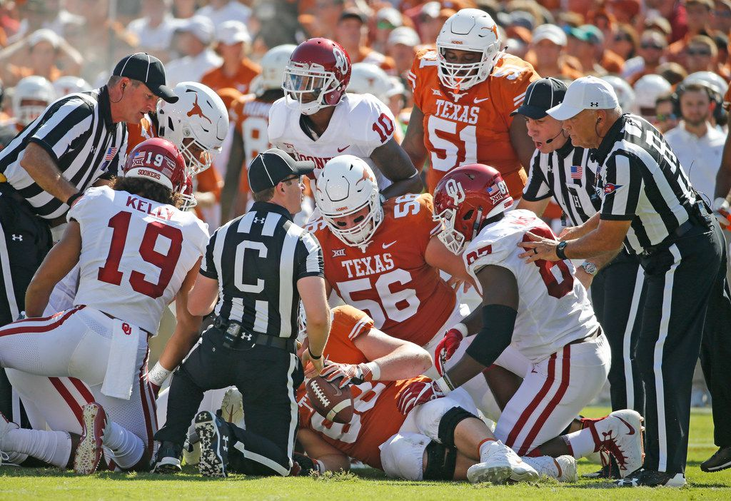 The officials try to determine possession after a first-quarter fumble during the Oklahoma University Sooners vs. the University of Texas Longhorns NCAA college football game at the Cotton Bowl in Dallas on Saturday, October 14, 2017. (Louis DeLuca/The Dallas Morning News)
