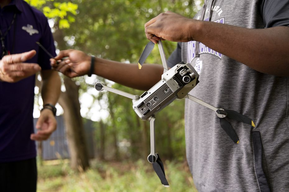 Stephen F. Austin Lumberjacks video coordinator Martin Oteng (right) shows coach Colby Carthel the damage a drone received after falling in the trees lining the practice field in Nacogdoches on Thursday, Oct. 8, 2020. (Juan Figueroa/ The Dallas Morning News)