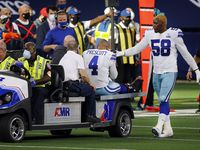 Dallas Cowboys defensive end Aldon Smith (58) comforts quarterback Dak Prescott (4) as he's carted off the field with an ankle injury against the New York Giants at AT&T Stadium Stadium in Arlington, Texas, Sunday, October 11, 2020.
