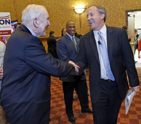 Ken Paxton (right), with U.S. Rep. Sam Johnson, has said through a spokesman that he would put his investments in a blind trust if he is elected attorney general.