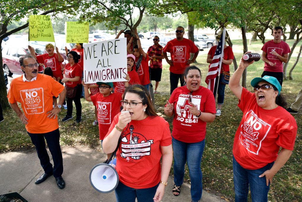 Maria Yolissa, 23, a member of the North Texas Dream Team, uses a megaphone to lead chants for Genoveva Castellanos, right, Zoila Chaver, far-right, and other pro immigration supporters, during a protest outside the offices of Republican state rep. Matt Rinaldi, Wednesday, May 31, 2017 in Farmers Branch.
