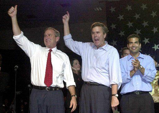 Then-presidential candidate George W. Bush, his brother, Florida Gov. Jeb Bush, and Jeb's son, George P. Bush, at a Miami rally in 2000
