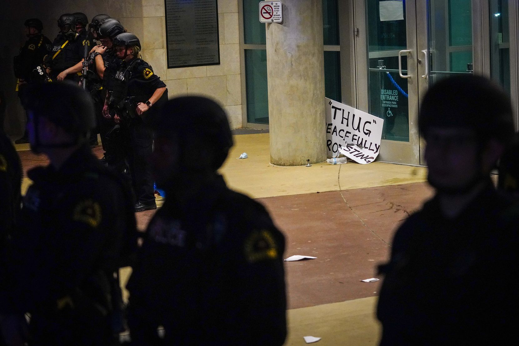 Dallas police form a line outside the front door of the the Dallas Police Headquarters as discarded signs pile up at the entrance during a protest against police brutality on Friday, May 29, 2020, in Dallas.