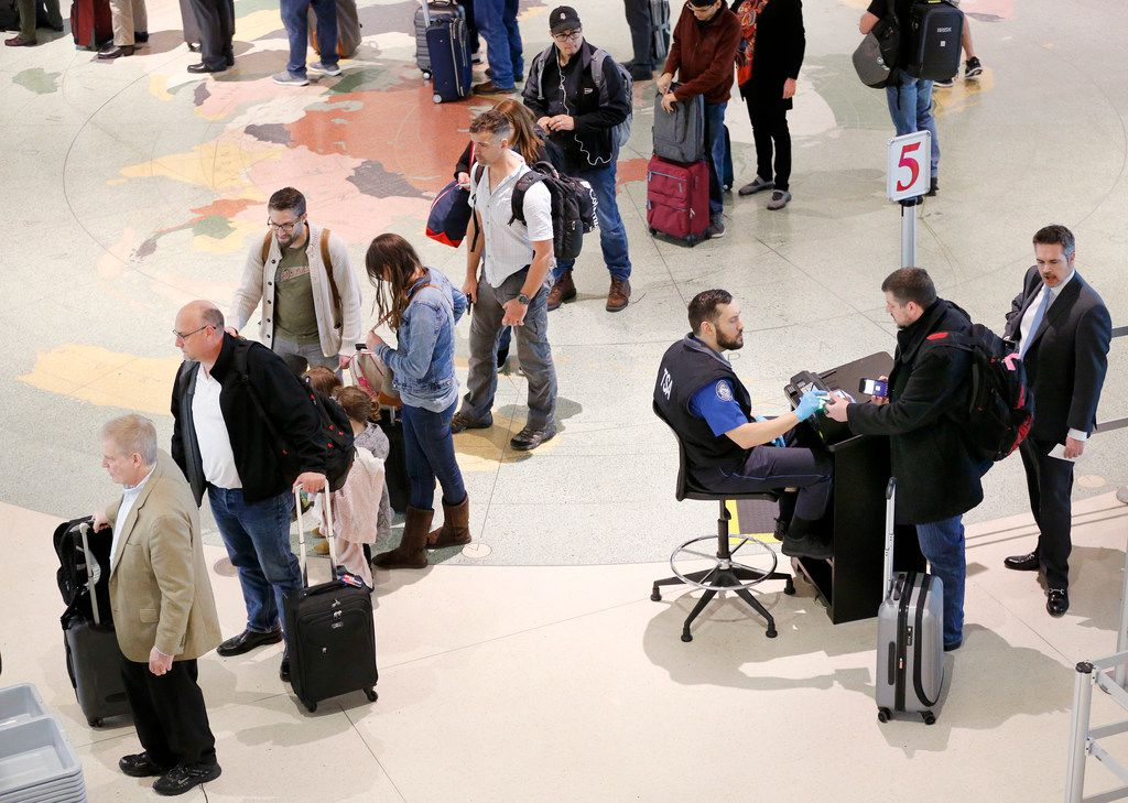 Airline passengers have their documents checked by TSA agents at Dallas Love Field Tuesday, Lines at Love Field reached a peak wait time of 41 minutes on Monday, the second-highest mark in the country behind Atlanta's Hartsfield-Jackson International Airport.  At DFW Airport, the longest waits reached 25 minutes, the sixth longest in the country.