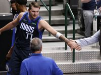 Dallas Mavericks guard Luka Doncic (77) reaches back for General Manager Donnie Nelson as they leave the floor with a lead at the half over the Cleveland Cavaliers at the American Airlines Center in Dallas, Friday, May 7, 2021. (Tom Fox/The Dallas Morning News)