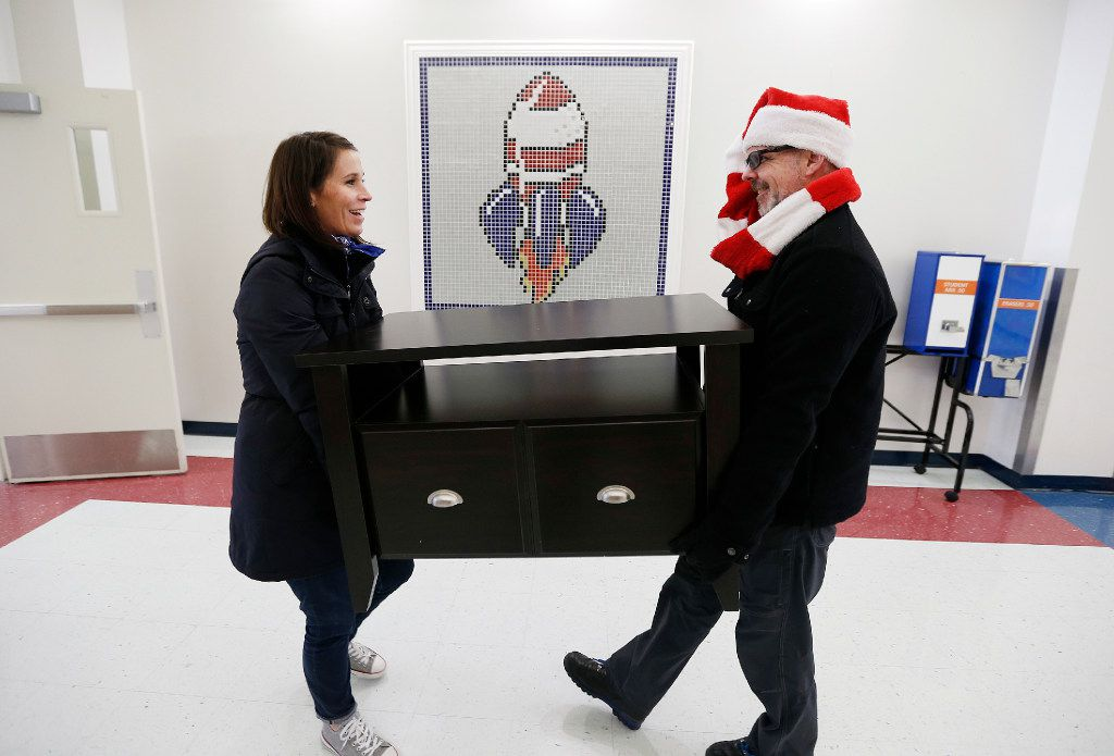 Hayley Heider (left) and Dave Rogers of Looney and Associates carry in a table for a nearly decorated teachers lounge at J.W. Ray Elementary School in Dallas, Thursday, December 8, 2016. The interior design firm raised money and donations to help redecorate two teacher lounges, provide a new laundry washer and dryer, school supplies and sports equipment.