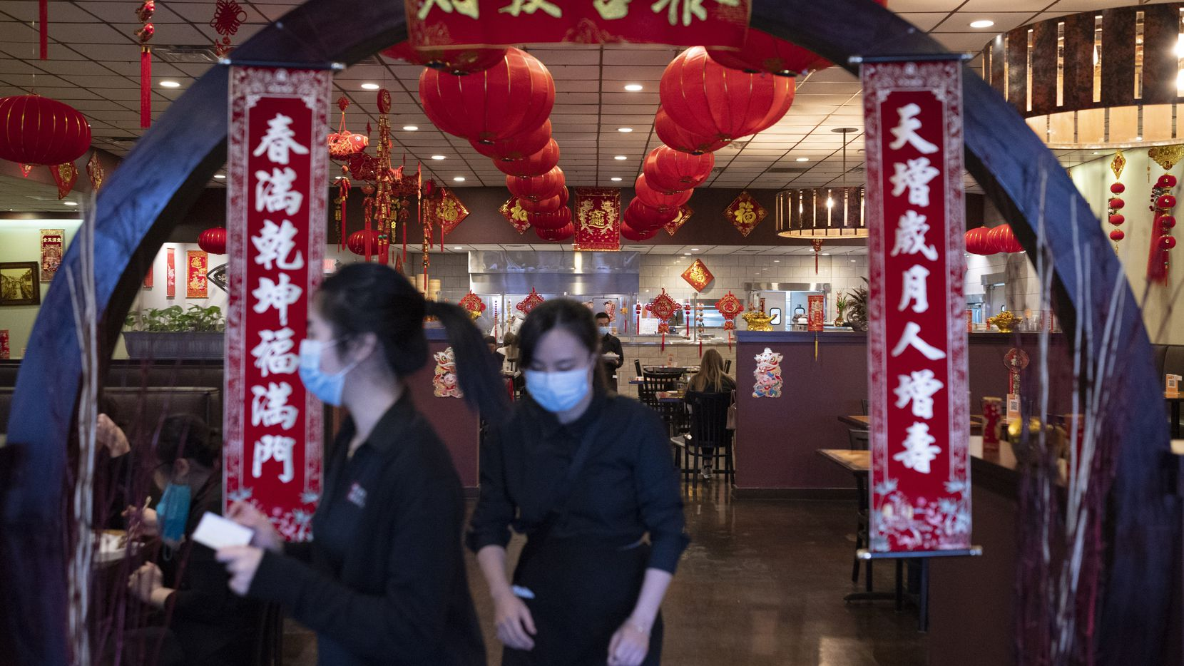 Employees wearing face masks walk towards the front to cater to customers inside Jeng Chi restaurant in Richardson during the COVID-19 pandemic, on Friday, Jan. 29, 2021.