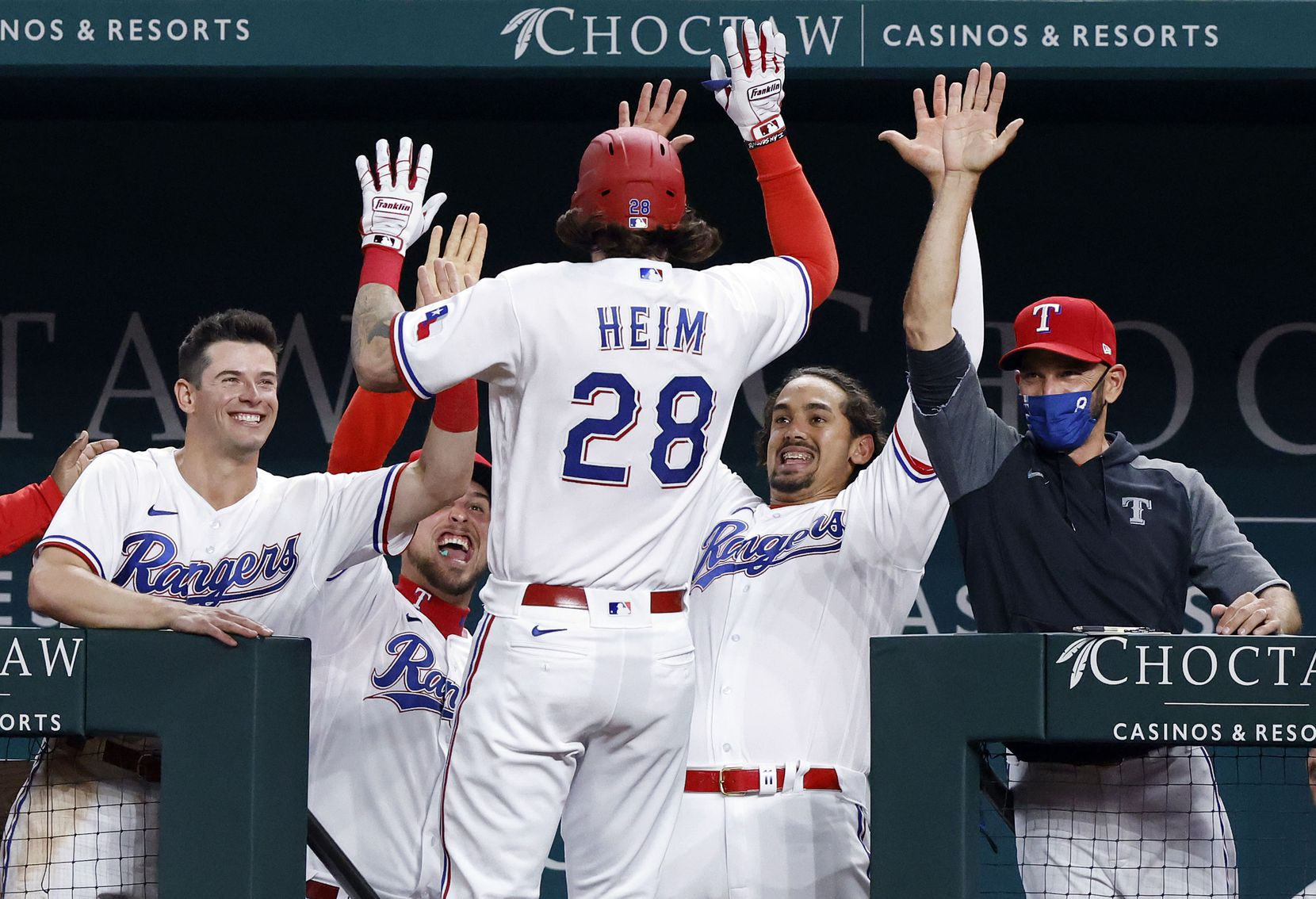 Texas Rangers Jonah Heim (28) is congratulated by manager Chris Woodward (right) and his teammates after hitting his first Major League home run during sixth inning against the Toronto Blue Jays at Globe Life Field in Arlington, Tuesday, April 7, 2021. (Tom Fox/The Dallas Morning News)