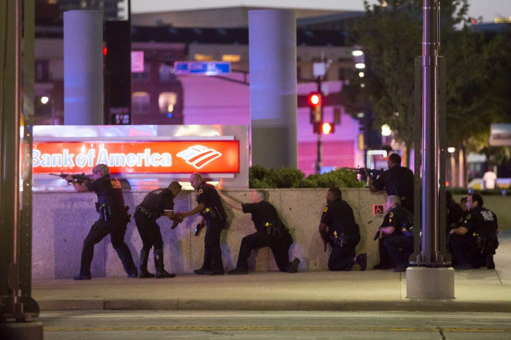 Dallas Police take up position along a wall at the corner of Lamar at Main as they train their weapons toward the El Centro campus after shots were fired during a Black Lives Matter rally in downtown Dallas on Thursday, July 7, 2016.