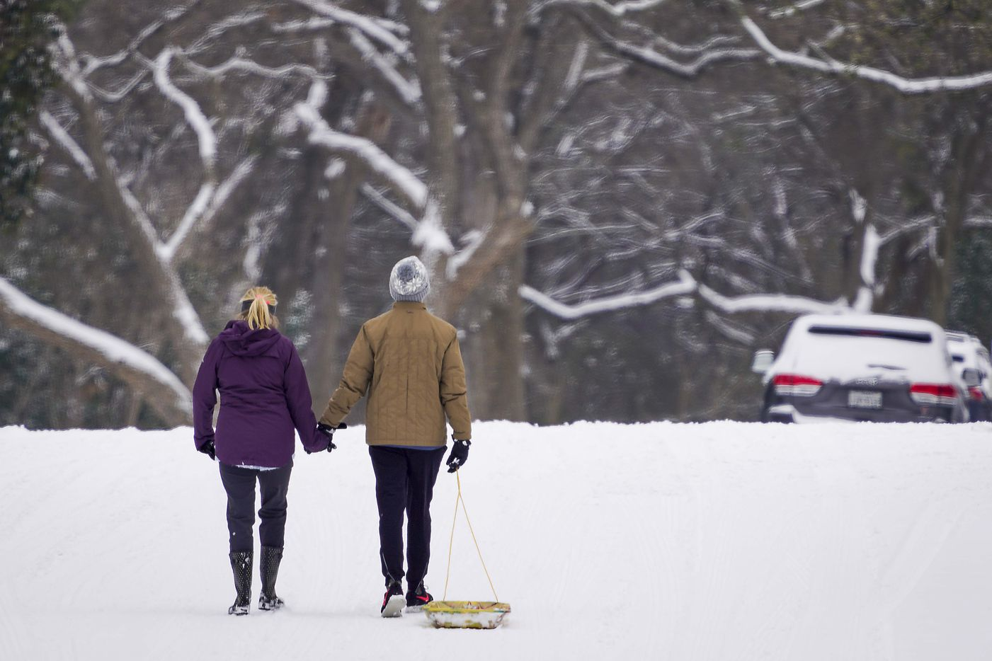 Josh and Amy Moore hold hands as the walk along the street alongside Prairie Creek Park after a second winter storm brought more snow and continued freezing temperatures to North Texas on Wednesday, Feb. 17, 2021, in Richardson.