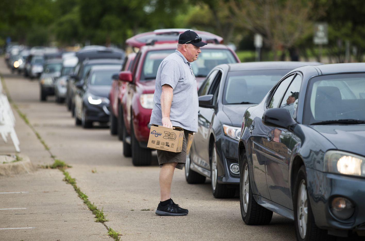 Volunteer Greg Cunningham approaches a car as it lines up receive food from the mobile pantry.