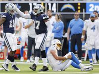 Dallas Cowboys linebacker Micah Parsons (11) is congratulated by defensive tackle Osa Odighizuwa (97) after his sack of Los Angeles Chargers quarterback Justin Herbert (right) during the fourth quarter at SoFi Stadium in Inglewood, California, Sunday, September 19, 2021. The Cowboys won, 20-17. (Tom Fox/The Dallas Morning News)