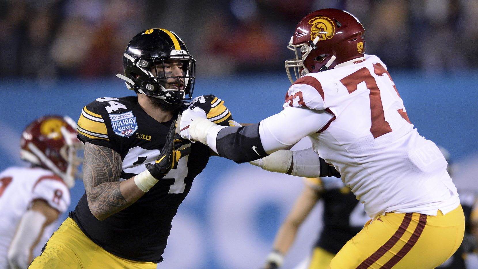 FILE - Iowa defensive end A.J. Epenesa (94) works against USC offensive tackle Austin Jackson (73) during the first half of the Holiday Bowl on Friday, Dec. 27, 2019, in San Diego. (AP Photo/Orlando Ramirez)