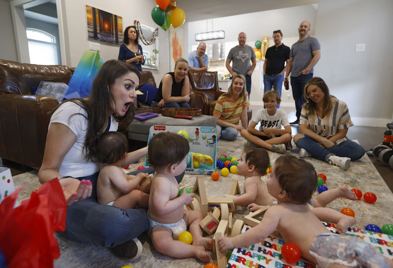 Jenny Marr helps open gifts for Harrison, Hardy, Henry, Hudson Marr as friends and family watch during their one year birthday party at their home on Monday, March 15, 2021in Grapevine, Texas.