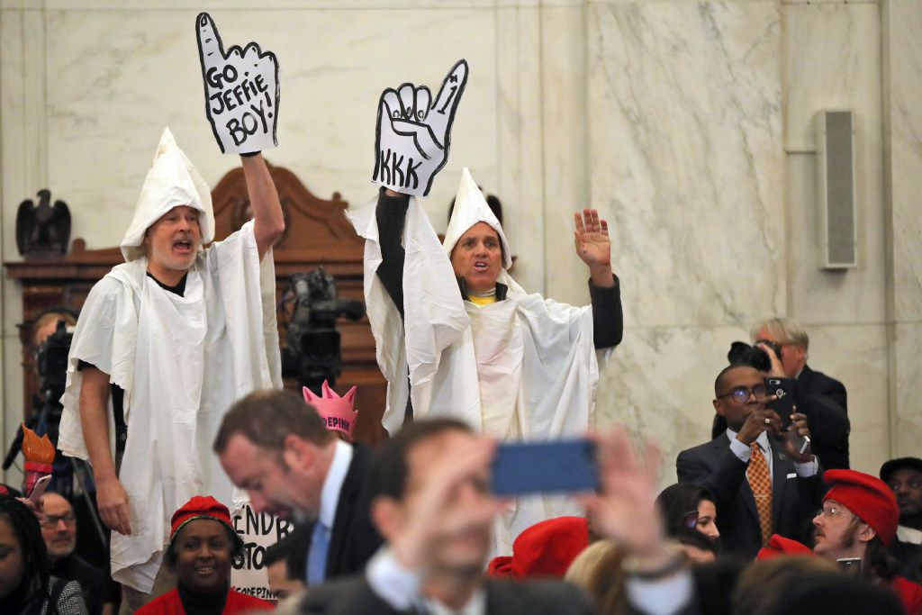 Demonstrators are seen on Capitol Hill  during the Senate Judiciary Committee's confirmation hearing for Sessions.