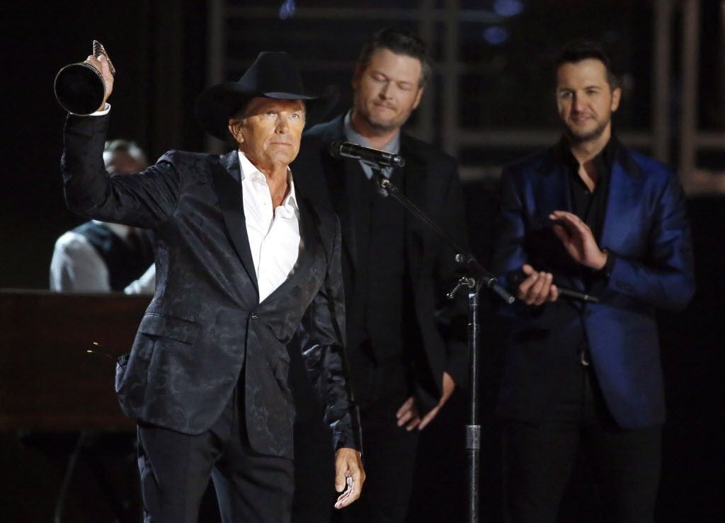 George Strait holds up his award during the 2015 Academy of County Music Awards Sunday, April 19, 2015 at AT&T Stadium in Arlington, Texas.