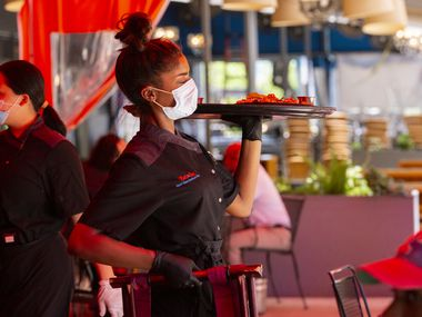 A server brings food to the outside patio of Beto & Son at Trinity Groves on May 1. Over 20% of workers in lodging and food services have filed for unemployment benefits in Texas, according to a Dallas Fed study. (Juan Figueroa/ The Dallas Morning News)