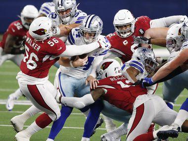 Dallas Cowboys quarterback Andy Dalton (14) is sacked by Arizona Cardinals linebacker Reggie Walker (56) and Arizona Cardinals outside linebacker Haason Reddick (43) during the third quarter of play at AT&T Stadium on Monday, October 19, 2020 in Arlington, Texas.