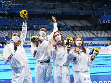 Bronze medallists (from R) USA's Erika Brown, USA's Abbey Weitzeil, USA's Natalie Hinds and USA's Simone Manuel pose after the final of the women's 4x100m freestyle relay swimming event during the Tokyo 2020 Olympic Games at the Tokyo Aquatics Centre in Tokyo on July 25, 2021.