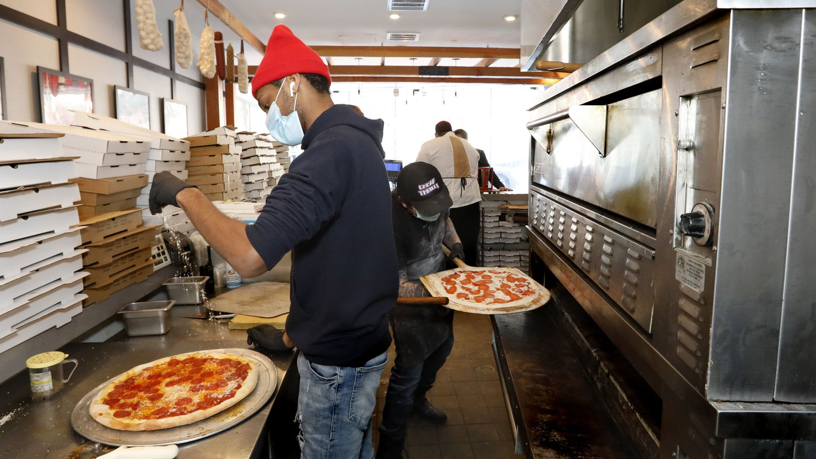 Jalen Holloway, left, puts cheese on a pizza as Jacob Walker, right, puts a pepperoni pizza in the oven at Sfereco in the Statler hotel on Friday, February 19, 2021, in downtown Dallas. The restaurant continued to sell food during the winter storm, when nearly every other restaurant in Dallas closed for at least one day.