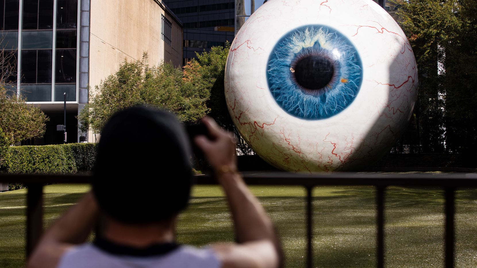 """Artist Tony Tasset's giant eyeball sculpture, """"Eye,"""" has been a popular attraction in Dallas since its debut in 2013. It was damaged on the night of May 29, when protesters tagged it with graffiti in the wake of George Floyd's death at the hands of Minneapolis police."""