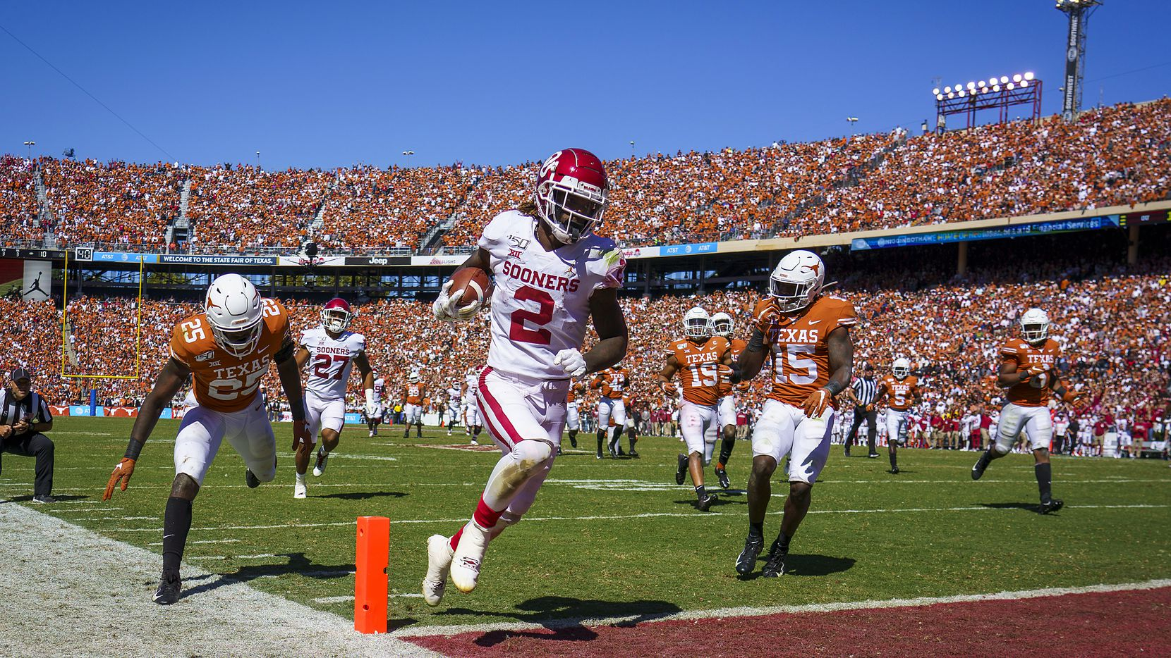 Oklahoma wide receiver CeeDee Lamb (2) scores on a 51-yard pass play past Texas defensives back B.J. Foster (25) and Chris Brown (15) during the second half of an NCAA football game at the Cotton Bowl on Saturday, Oct. 12, 2019, in Dallas. Oklahoma won the the game 34-27.