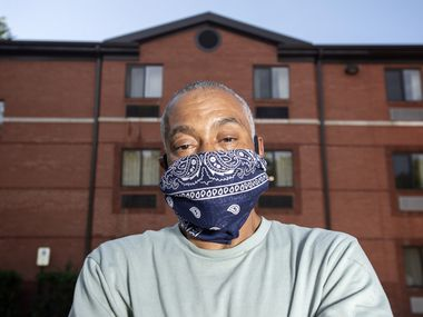 Terry Thompson poses for a portrait outside the extended stay hotel where he lives with his 10-year-old son, Monday, May 4, 2020 in Dallas. Thompson, who cleaned carpets for restaurant chains before the coronavirus outbreak, was laid off in March, and is in the process of receiving housing assistance from the non-profit Housing Crisis Center.