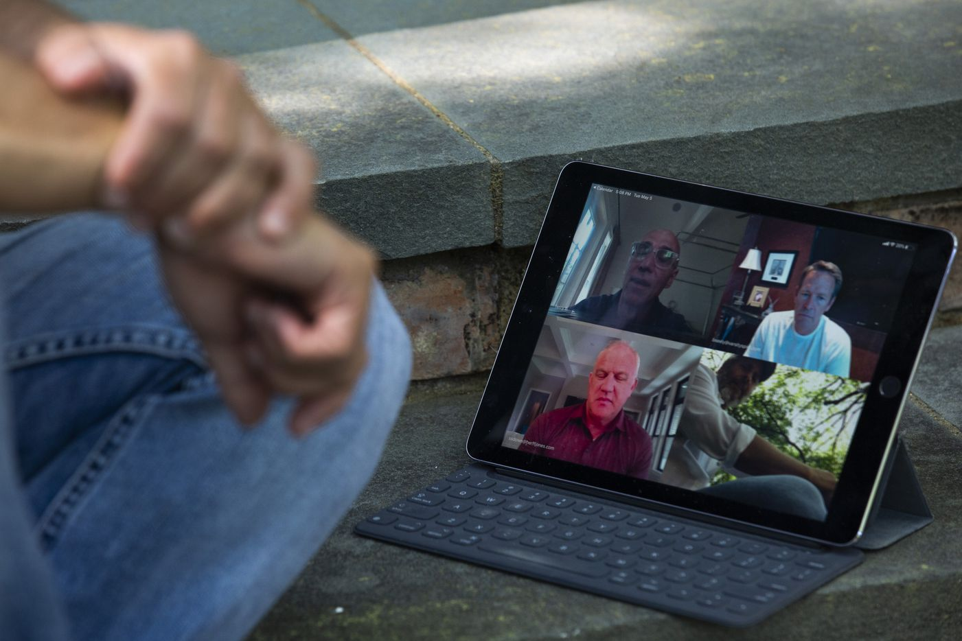 Adam Blumenfeld, CEO of Varsity Brands, participates in a Zoom video conference meeting with colleagues during a portrait session outside of his home in Dallas on May 5.