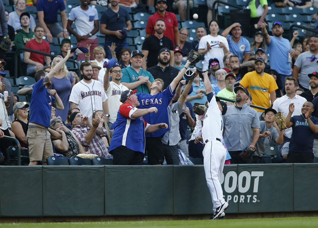 SEATTLE, WA - JULY 22: Kyle Seager #15 of the Seattle Mariners gets tangled up with fans while trying to catch a foul ball hit by Hunter Pence #24 of the Texas Rangers in the first inning at T-Mobile Park on July 22, 2019 in Seattle, Washington. (Photo by Lindsey Wasson/Getty Images)