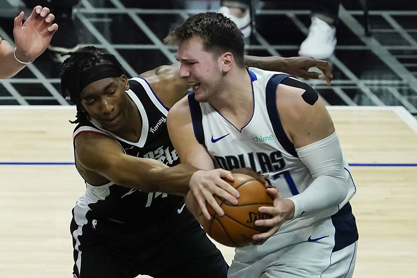 Dallas Mavericks guard Luka Doncic (77) wrestles a rebound away from LA Clippers guard Terance Mann (14) during the fourth quarter of an NBA playoff basketball game at the Staples Center on Wednesday, June 2, 2021, in Los Angeles. The Mavericks won the game 105-100. (Smiley N. Pool/The Dallas Morning News)
