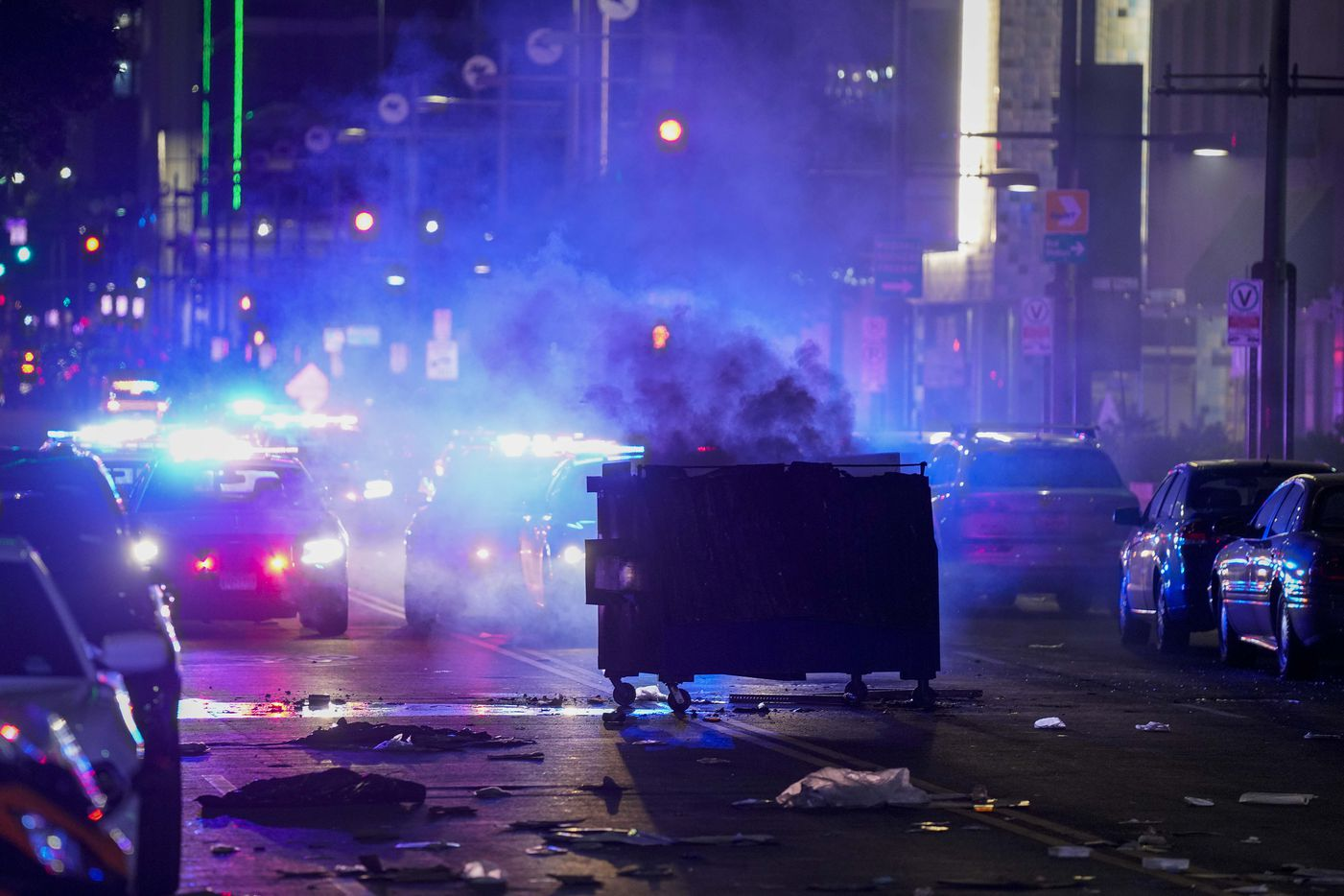 A dumpster smolders as debris covers the middle of Main Street downtown following a protest against police brutality in the early morning hours of Saturday, May 30, 2020, in Dallas.