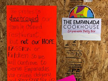 A sign on the boarded up door of Empanada Cookhouse in Downtown Dallas