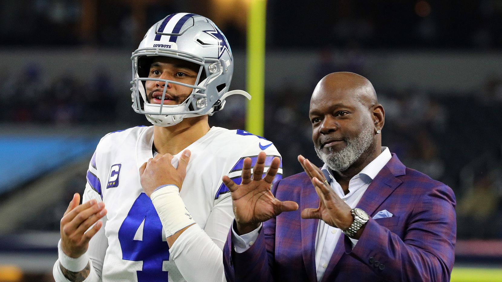 Dak Prescott of the Dallas Cowboys waits for the ball with former Cowboys running back Emmitt SMith before the game against the Buffalo Bills at AT&T Stadium on November 28, 2019 in Arlington, Texas.