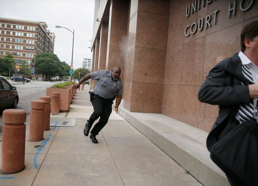 A security guard and a civilian run for cover as bullets ricochet off the building as a shooter (far background left) fires toward them on Monday, June 17, 2019, at the Earle Cabell Federal Building in Dallas.